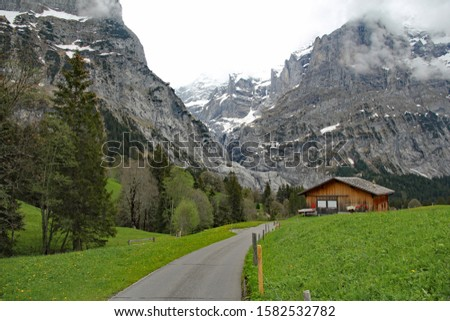 Quiet country road passes dramatic Swiss Alpine mountain landscape with a farm hut surrounded by lush wildflower meadows on the way down the Grosse Scheidegg pass towards Grindelwald #1582532782