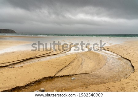 Sandy beach in winter in Brittany. Water flowing from a river digs channels that reach the ocean. The rainy sky is reflected in the bodies of water. #1582540909