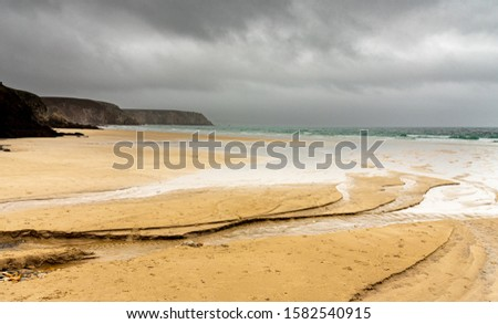 Sandy beach in winter in Brittany. Water flowing from a river digs channels that reach the ocean. The rainy sky is reflected in the bodies of water. #1582540915