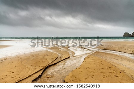 Sandy beach in winter in Brittany. Water flowing from a river digs channels that reach the ocean. The rainy sky is reflected in the bodies of water. #1582540918