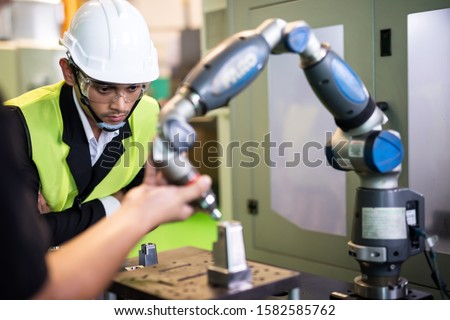 Waist up inspector manager check robot lathe machine hand in metal manufacturing factory. Manufacturing industry with modern equipment tool to produce car spare part. #1582585762
