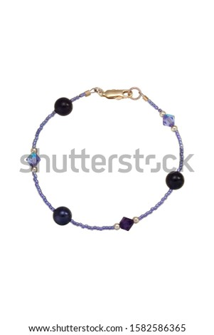 Round black beads and pearl, bicone dichroic lavender and purple crystals, lavender seed beads and silver and gold findings make up this bead bracelet. Shown on a white background. #1582586365