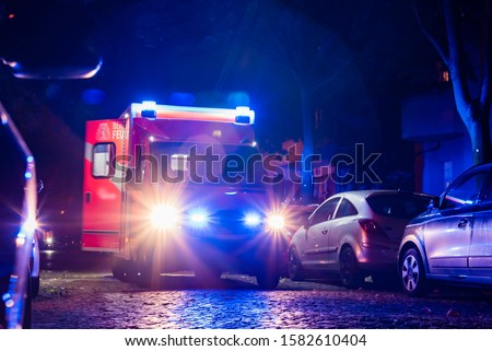 Out of focus photographed ambulance, ambulance in action, symbol pictures, abstract, blue light at night, fire department, berlin, germany