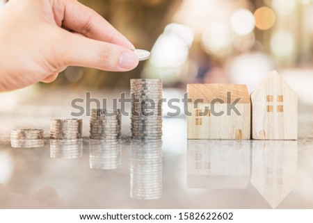 Hand choosing row of coin money on wood table and mini wood house, selective focus, Planning to buy property. Choose what's the best. A symbol for construction ,ecology, loan concepts #1582622602