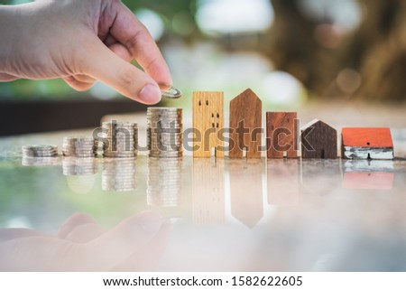 Hand choosing row of coin money on wood table and mini wood house, selective focus, Planning to buy property. Choose what's the best. A symbol for construction ,ecology, loan concepts #1582622605