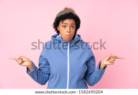 African american woman with winter hat over isolated pink background pointing to the laterals having doubts #1582690204
