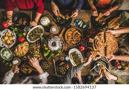 Traditional Turkish family celebration dinner. Flat-lay of people eating Turkish salads, cooked vegetables, meze starters and borek pie and drinking raki drink, top view. Middle Eastern cuisine #1582694137