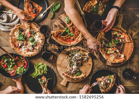Family or friends having pizza party dinner. Flat-lay of people eating different kinds of Italian pizza, salad and drinking wine over wooden table, top view. Fast food lunch, gathering, celebration #1582695256