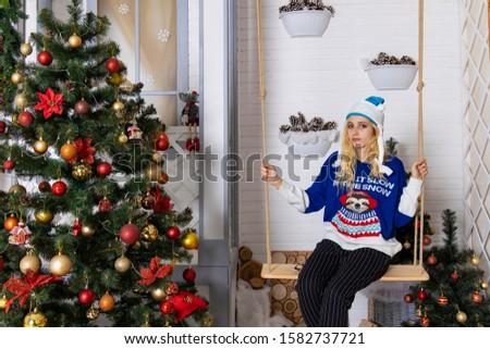 shy teenage girl portrait on swing in Christmas decoration studio room  #1582737721