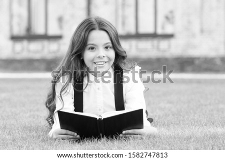 Reading is passport to world. Happy little girl enjoy reading book on green grass. Cute small child learn reading at primary school. Book is worth reading. School library. Knowledge and information. #1582747813