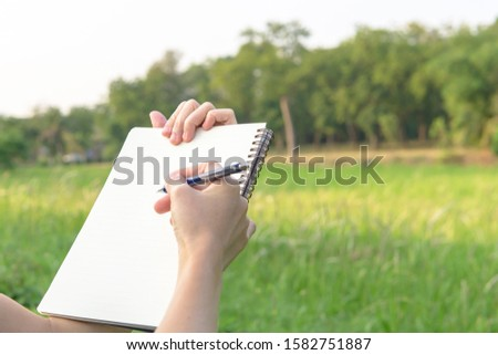 Hand holding notebook and pencil to work in the park. #1582751887
