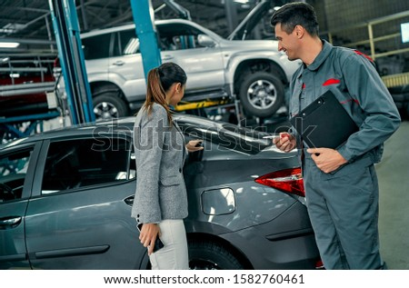 Beautiful businesswoman and auto service mechanic are discussing the work. Car repair and maintenance. #1582760461
