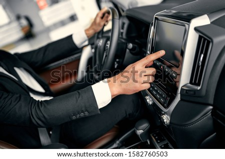 Transport, destination, modern technology and people concept - male hand searching for route using navigation system on car dashboard screen #1582760503