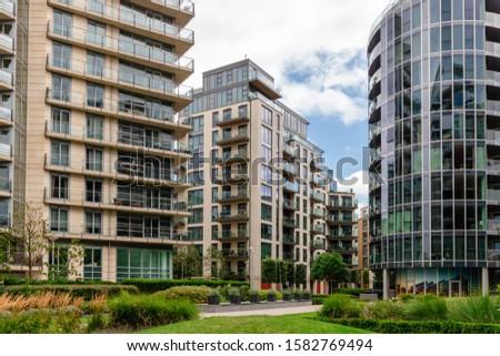 Green garden within modern apartment building complex #1582769494