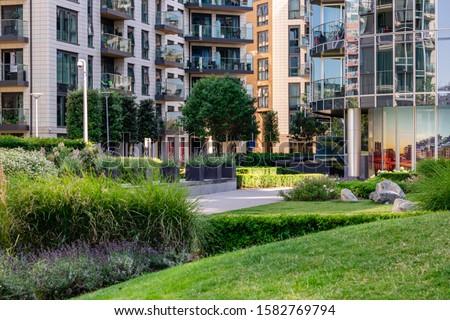Green garden within modern apartment building complex #1582769794