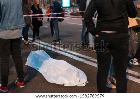 Human body covered by a sheet lying on the street. Royalty-Free Stock Photo #1582789579
