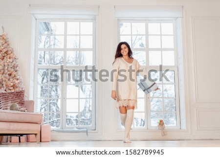 Beautiful young girl in white dress posing on camera. Christmas concept #1582789945