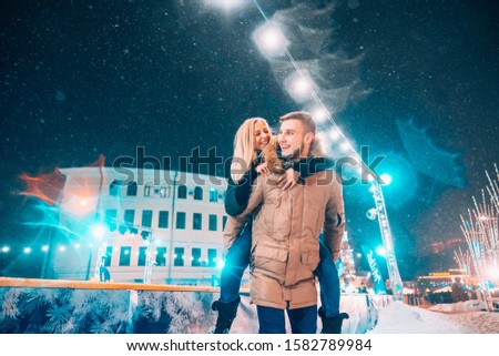 Cheerful and playful couple in warm winter outfits are fooling around #1582789984