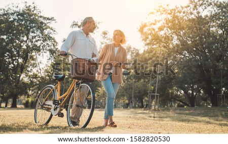 Beautiful Senior couple walking their bike along happily talking in park.mature couple in summer park.Elderly man and old woman with bicycles outside in spring nature. #1582820530