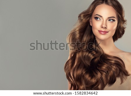 Beauty brunette girl with long  and   shiny wavy black hair .  Beautiful   woman model with curly hairstyle . #1582834642