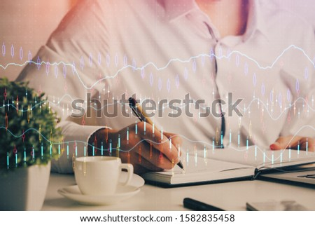 Double exposure of man's hands writing notes of stock market with forex chart. #1582835458