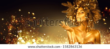 Christmas golden Woman. Winter girl pointing Hand, blowing blinking stars,  Beautiful New Year, Christmas Tree Holiday Hairstyle and gold skin Makeup. Gift. Girl in decorated Xmas wreath. Beauty Model #1582863136