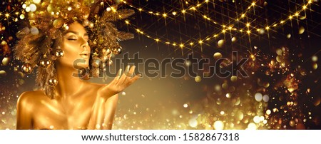 Christmas golden Woman. Winter girl pointing Hand, blowing blinking stars,  Beautiful New Year, Christmas Tree Holiday Hairstyle and gold skin Makeup. Gift. Girl in decorated Xmas wreath. Beauty Model #1582867318