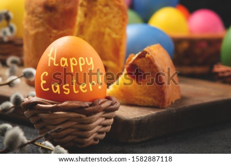 Egg with the inscription Happy Easter in a wicker stand, Easter cake on a cutting board and painted eggs on the table - traditional Easter breakfast