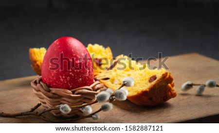 Red Easter egg in wisker stand and slice of Easter cake on a cutting board on a dark table - traditional Easter breakfast