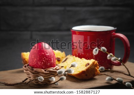 Red Easter egg, a slice of Easter cake and a cup of coffee on a cutting board on a dark table - traditional Easter breakfast