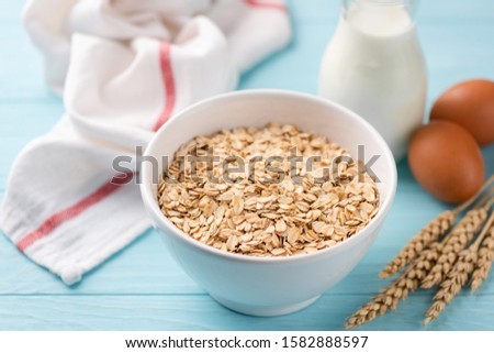 Oats, milk and eggs on blue wooden table. Food ingredients for a healthy breakfast #1582888597