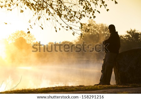 This foggy morning and quite lake makes for an inspirational location for this adult male to contemplate life's challenges and rewards in a quiet setting. Royalty-Free Stock Photo #158291216