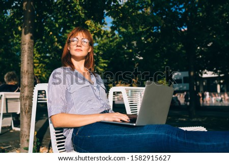 Beautiful redhead woman freelancer closing eyes protecting from sunrays while using technology in park in sunbed, attractive female student share media and publications via laptop resting outdoors #1582915627