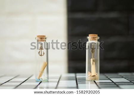 Tiny boat anchor and tiny keys in tiny glass bottles #1582920205