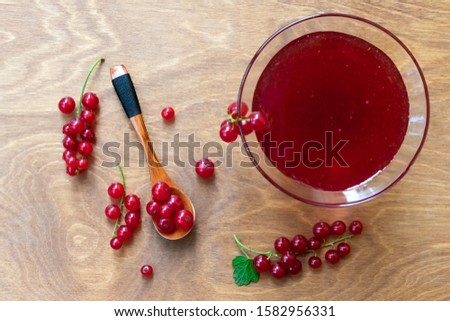 Glass bowl of red current jam with wooden spoon full of many ripe juicy red current berries on dark wooden table background. Marmalade made of fresh red current #1582956331