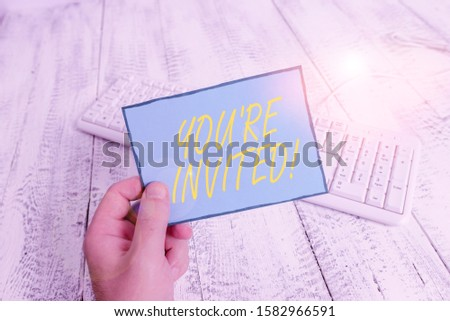 Writing note showing You Re Invited. Business photo showcasing make a polite friendly request to someone go somewhere Man holding colorful reminder square shaped paper wood floor. #1582966591