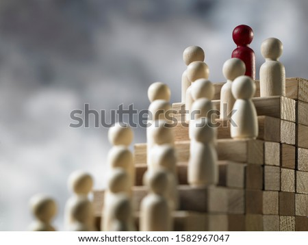 red Figurine Leading Human Figures On Top Of Wooden Blocks #1582967047
