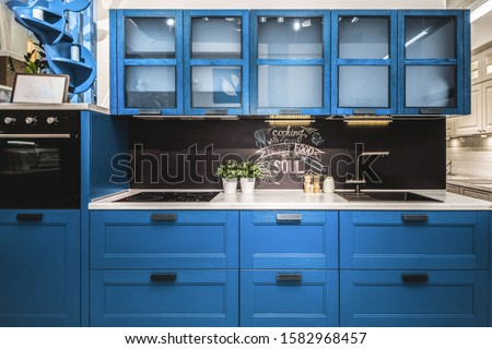 Modern red kitchen interior with black brick walls, wooden countertops with a built in sink and a cooker.  color of the year 2020 pantone classic blue Royalty-Free Stock Photo #1582968457