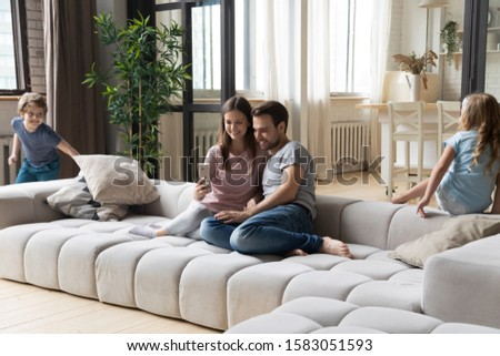 In modern cozy living room full family young couple sit on couch hold cellphone make call, purchasing using e-commerce while kids running play tag game, homeowners weekend activity at new home concept #1583051593