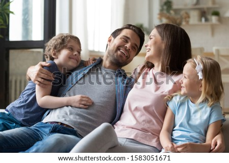 Preschooler adorable kids and their parents resting sitting on couch in living room, couple and children spend weekend together laughing enjoy communication, happy family portrait and new home concept #1583051671