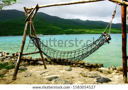 A place of rest and relaxation on the ocean. Hammock on posts on the ocean coast. Close-up. In the background a speedboat and jet ski, in the distance the coast of a tropical island. #1583054527