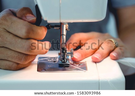 Sewing process, close up seamstress hands sew white  clothes with sewing machine. #1583093986