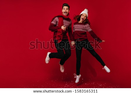 Man and woman in knitted sweaters happily jumping, holding hands on red background #1583165311