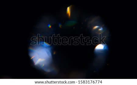 Lens Flare, Abstract Bokeh Lights. Leaking Reflection of a Glass, Crystal, Defocused Shining Colorful rainbow Light Leaks, Rays on Black Background #1583176774