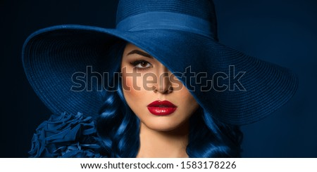 Portrait of a beautiful woman with red lips in a hat, toned in color of the year 2020, classic blue. Royalty-Free Stock Photo #1583178226