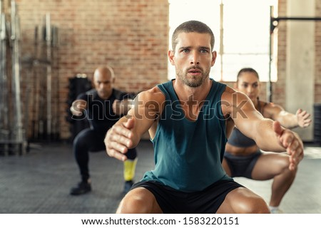 Young man exercising with squat in gym with people in background. Fit man exercising with stretched hands and squats at gym. Fitness class squatting togeher with outstretched during an exercise. #1583220151
