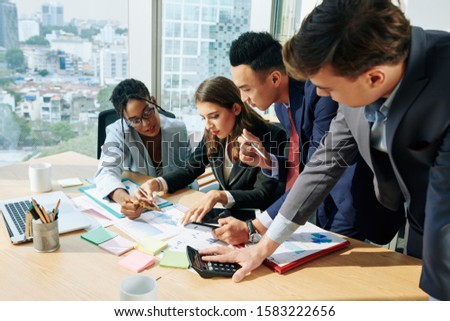 Serious business team gathered together at office table to discuss annual financial report #1583222656