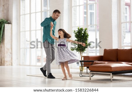Happy loving father leading in dance holding daughter hand up. Smiling dad and adorable daughter dancing to favorite song at home. Having fun together in living room, family weekend concept. #1583226844
