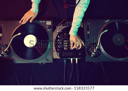 Dj hands on equipment deck and mixer with vinyl record at party Royalty-Free Stock Photo #158323577