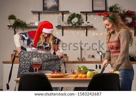 Two young women prepare food for New Year in kitchen #1583242687